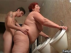 Huge lady takes it unfamiliar behind in the public restroom